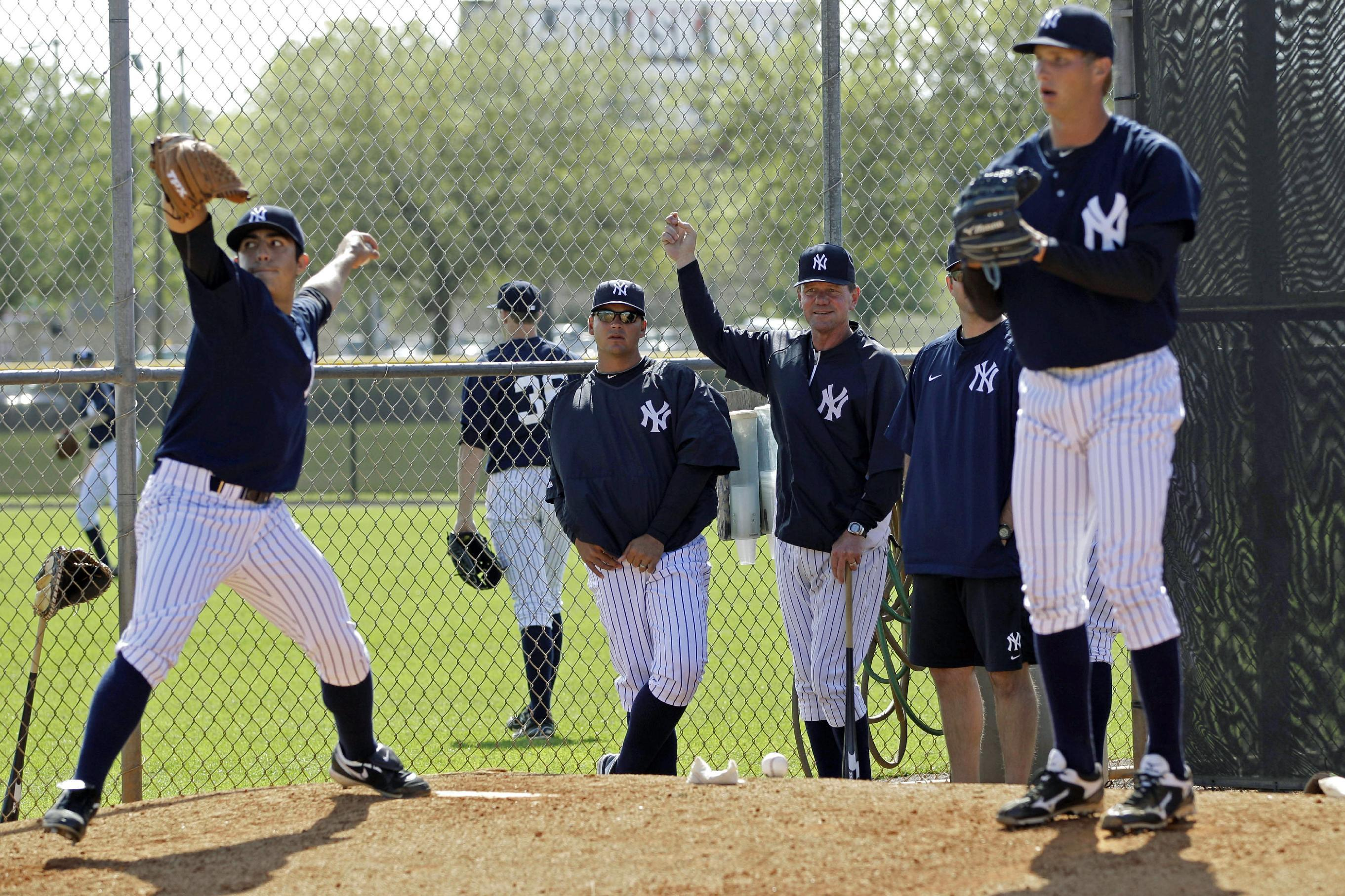 In this Wednesday, March 7, 2012, photo, Scranton/Wilkes-Barre Yankees manager Dave Miley, third from left, watches pitchers throw in the bullpen at the Yankees' minor league training complex in Tampa, Fla. Miley's team will play 144 games of their Triple-A season on the road this year, forced out of PNC Field because of a $40 million stadium renovation. (AP Photo/Kathy Willens)
