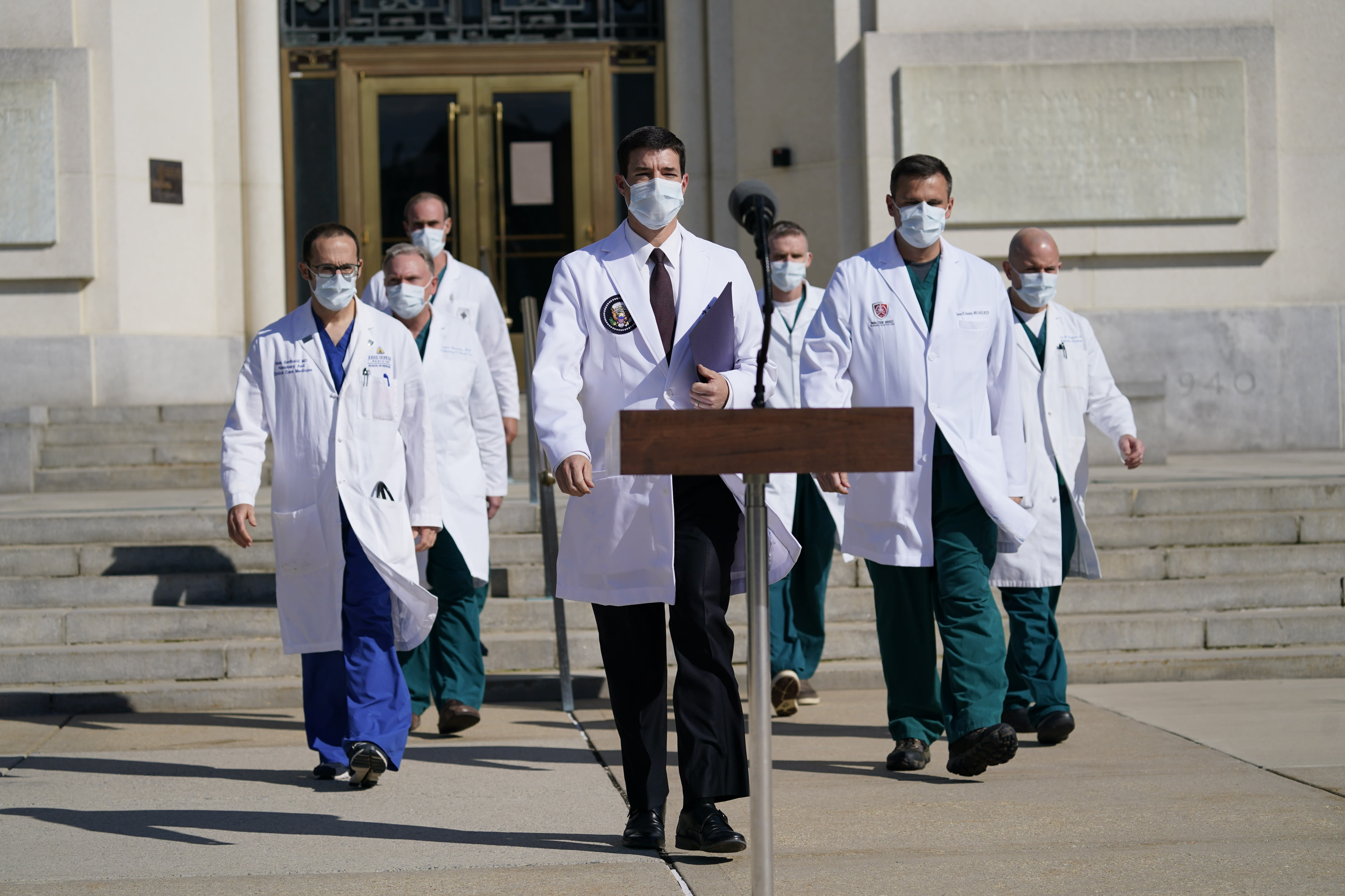 Dr. Sean Conley, physician to President Donald Trump, center, and other doctors, walk out to talk with reporters at Walter Reed National Military Medical Center, Monday, Oct. 5, 2020, in Bethesda, Md. (AP Photo/Evan Vucci)
