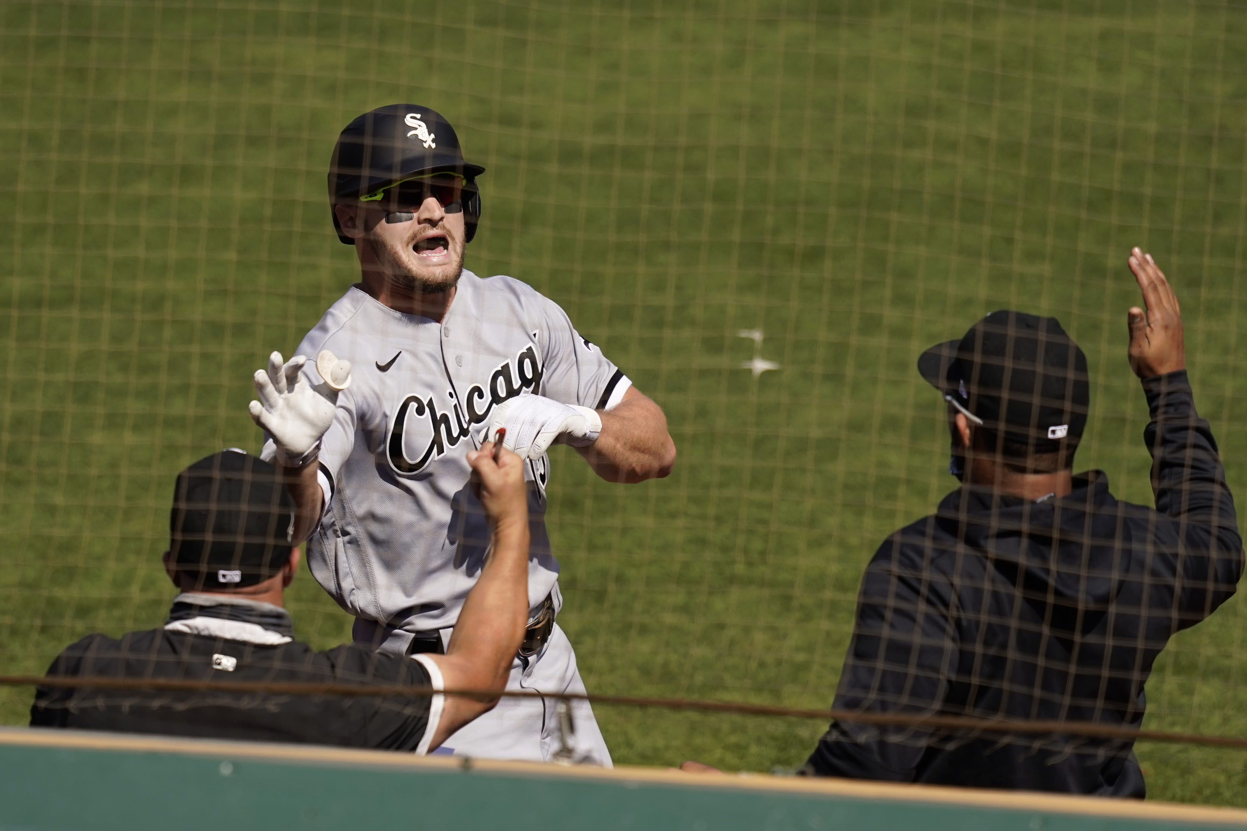 Chicago White Sox's Adam Engel, facing, is congratulated by teammates after hitting a solo home run against the Oakland Athletics during the second inning of Game 1 of an American League wild-card baseball series Tuesday, Sept. 29, 2020, in Oakland, Calif. (AP Photo/Eric Risberg)