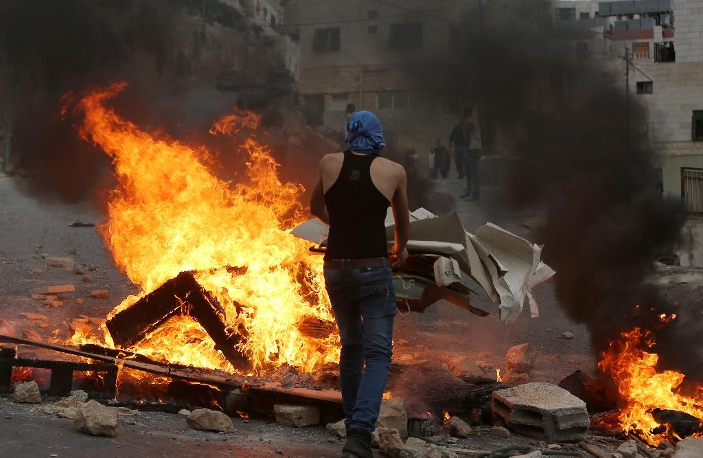 A Palestinian young man burns cardboard during clashes with Israeli security forces who search for the suspected Palestinian killers of a Jewish settler couple on October 6, 2015 in the West Bank city of Nablus