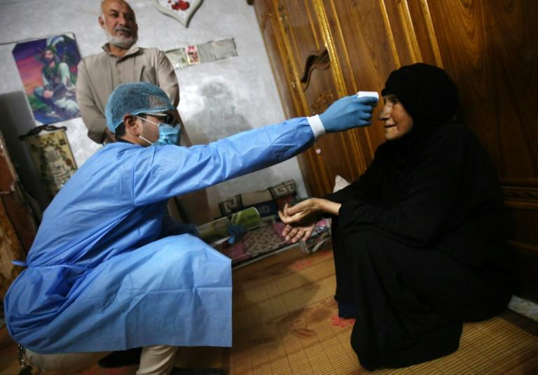 An Iraqi public hospital doctor checks a woman's temperature for COVID-19 in the capital Baghdad's suburb of Sadr City earlier this year (AFP Photo/AHMAD AL-RUBAYE)