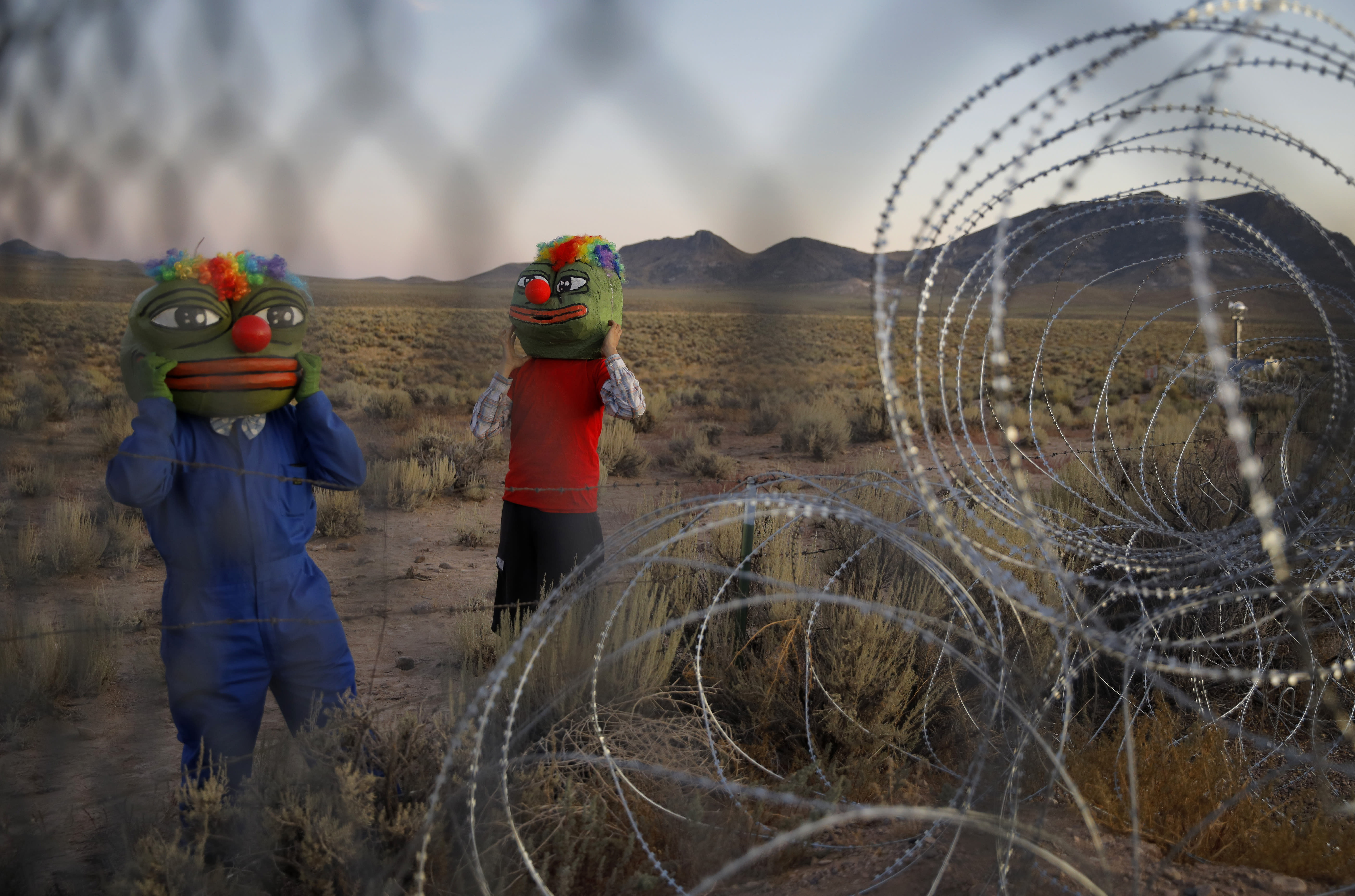 """Martin Custodio, left, and Rafael Castillo wear Pepe masks while standing near razor wire at an entrance to the Nevada Test and Training Range near Area 51, Friday, Sept. 20, 2019, near Rachel, Nev. People came to visit the gate inspired by the """"Storm Area 51"""" internet hoax. (AP Photo/John Locher)"""