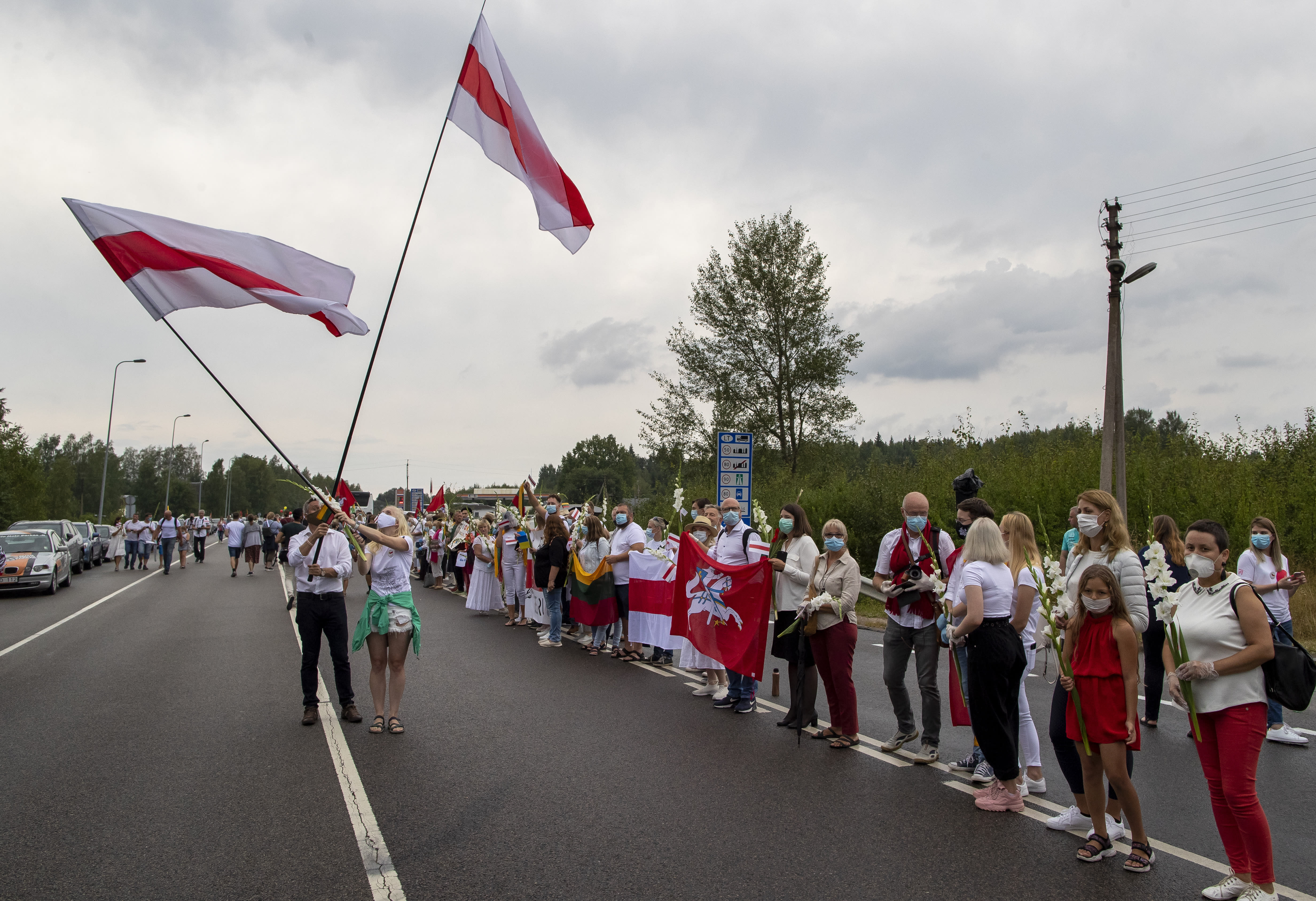 "Supporters of Belarus opposition from Lithuania hold and wave historical Belarusian flags during the ""Freedom Way"", a human chain of about 50,000 strong from Vilnius to the Belarusian border, near Medininkai, Lithuanian-Belarusian border crossing east of Vilnius, Lithuania, Sunday, Aug. 23, 2020. In Aug. 23, 1989, around 2 million Lithuanians, Latvians, and Estonians joined forces in a living 600 km (375 mile) long human chain Baltic Way, thus demonstrating their desire to be free. Now, Lithuania is expressing solidarity with the people of Belarus, who are fighting for freedom today. (AP Photo/Mindaugas Kulbis)"