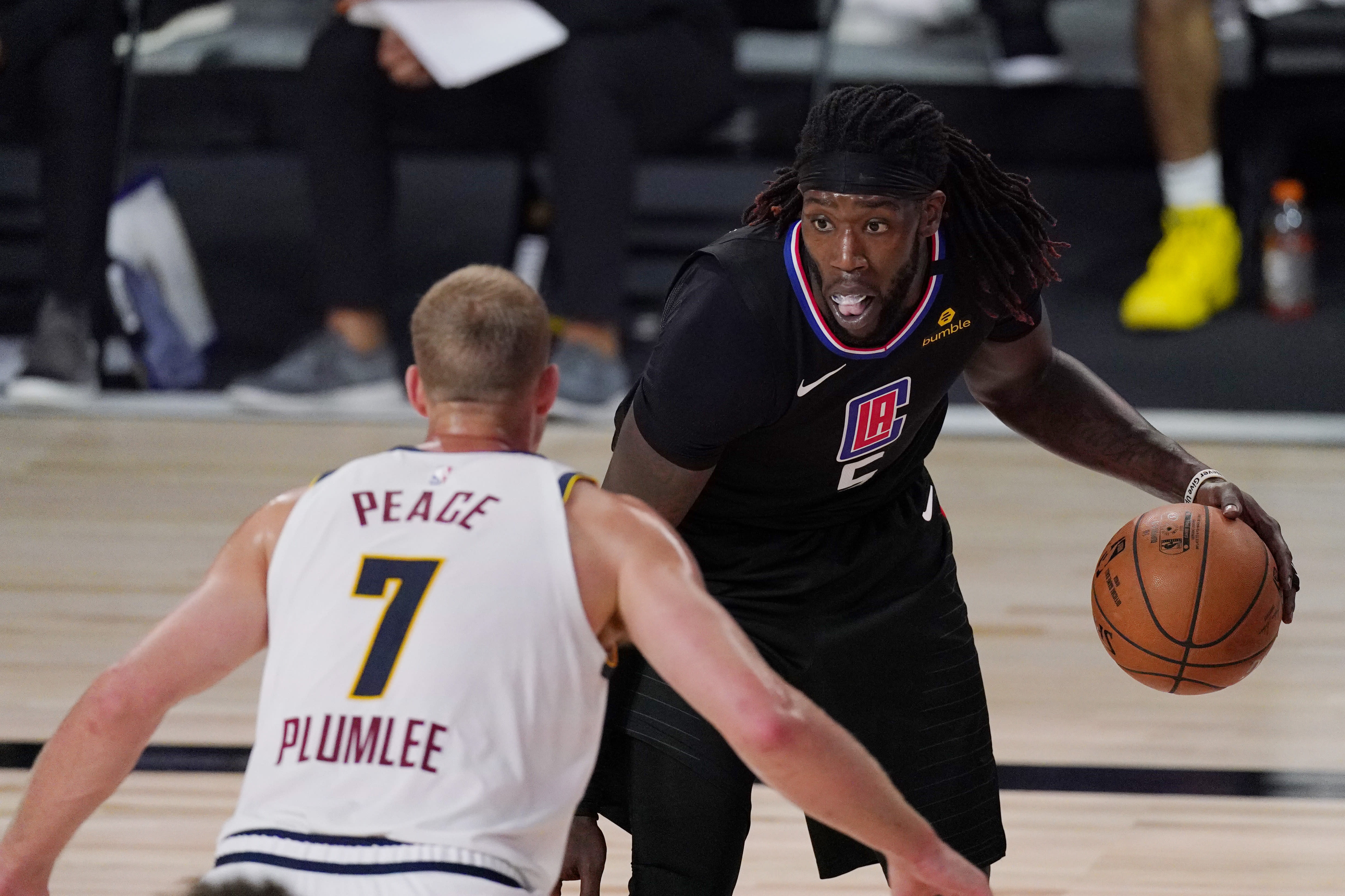 Los Angeles Clippers' Montrezl Harrell (5) is defended by Denver Nuggets' Mason Plumlee (7) in the second half of an NBA conference semifinal playoff basketball game Thursday, Sept 3, 2020, in Lake Buena Vista Fla. (AP Photo/Mark J. Terrill)