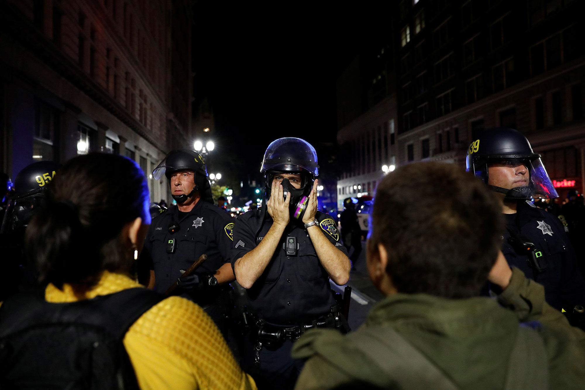 <p>A police officer deploys his gas mask during a demonstration following the election of Donald Trump as President of the United States in Oakland, Calif., on Nov. 10, 2016. (Photo: Stephen Lam/Reuters) </p>