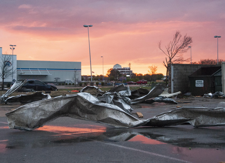 Debris covers a parking lot as the sun sets after a tornado in Jonesboro, Ark., Saturday, March 28, 2020. (Quentin Winstine/The Jonesboro Sun via AP)