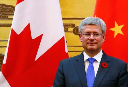 Canada's Prime Minister Harper stands in front of Chinese and Canadian national flags as he witnesses a signing ceremony at the Great Hall of the People in Beijing
