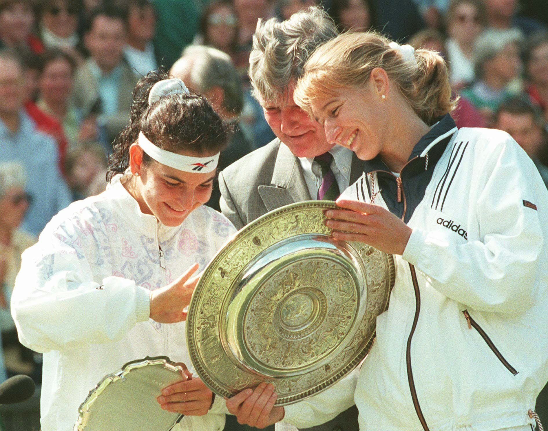 FILE - In this July 6, 1996, file photo, 1996 women's singles champion Steffi Graf, right, examines the the winners trophy with the runner up, Arantxa Sanchez-Vicario, left and Tournament referee Alan Mills after the presentation ceremony on Wimbledon's Centre Court. Graf won the match in straight sets 6-3, 7-5 to capture her seventh singles title. (AP Photo/Dave Caulkin, File)