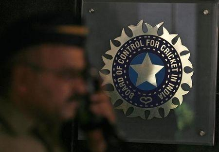 A policeman walks past logo of BCCI in Mumbai