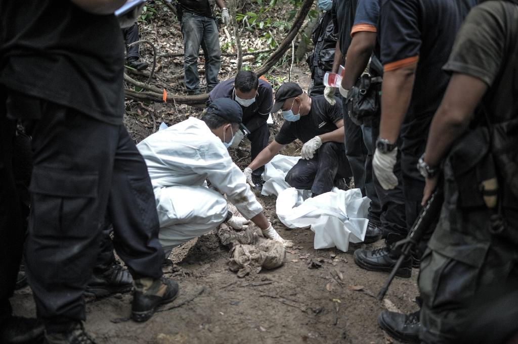 Malaysian police exhume dozens of graves found in a series of remote human-trafficking camps along the Thai border last year (AFP Photo/Mohd Rasfan)