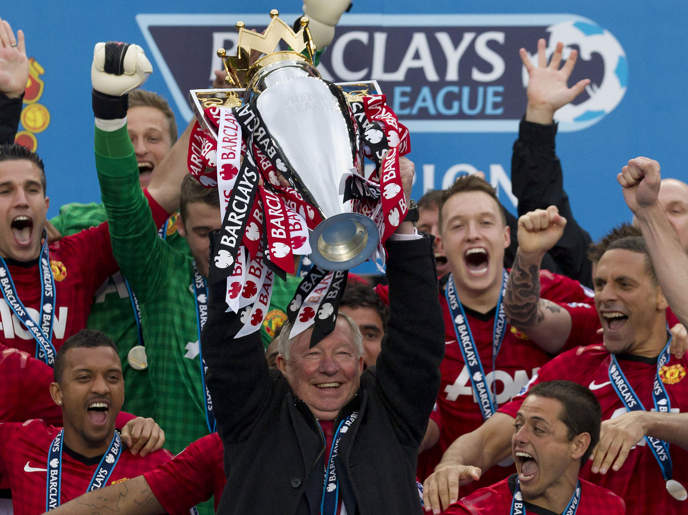 Manchester United's manager Sir Alex Ferguson, center, lifts the premier league trophy after his last home game in charge of the club, their English Premier League soccer match against Swansea City, at Old Trafford Stadium, Manchester, England, Sunday May 12, 2013. (AP Photo/Jon Super)