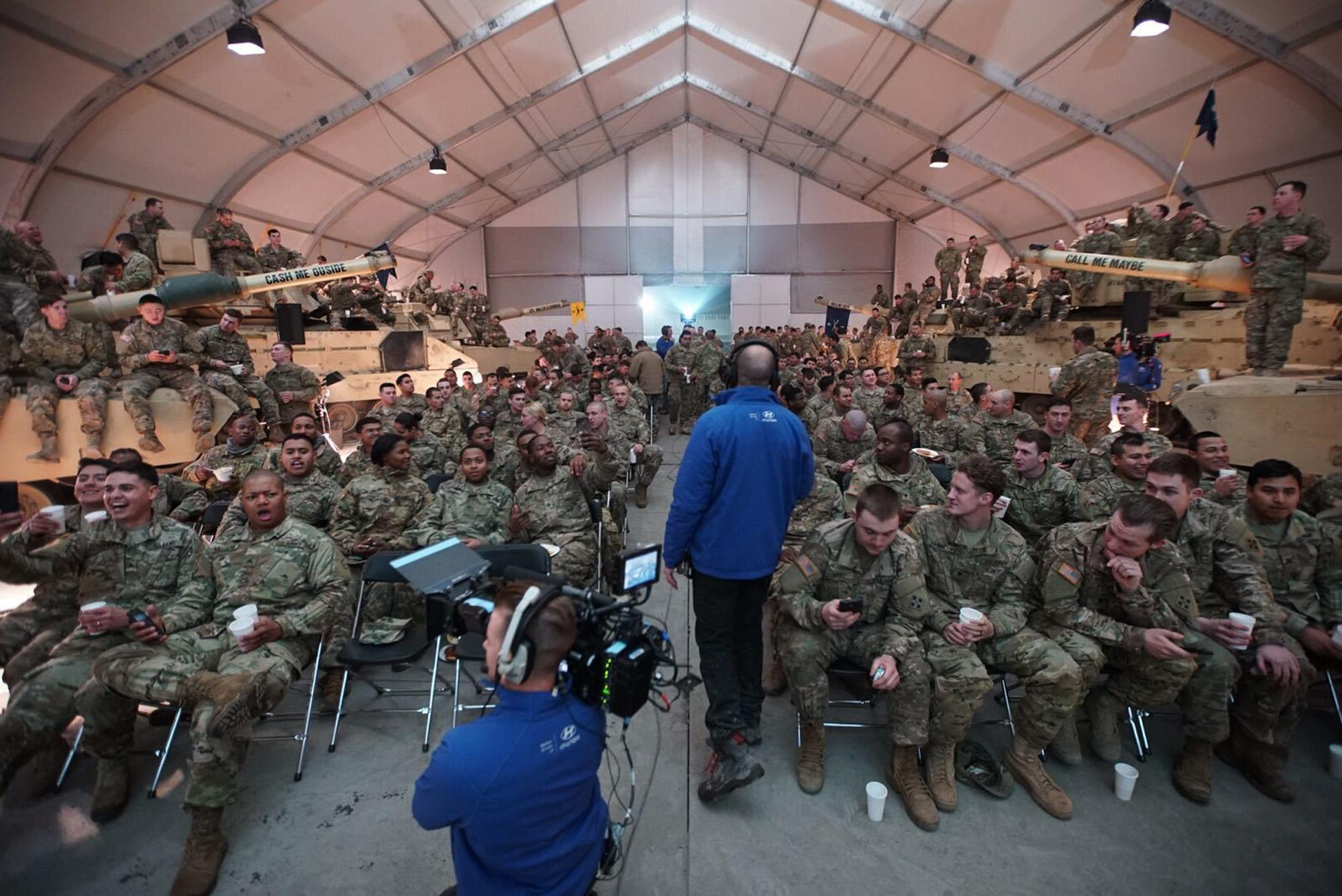 This image made from a video provided by Hyundai Motor America shows U.S. troops on U.S. military base in Zagan, Poland, watching Super Bowl 51 football game between the Atlanta Falcons and the New England Patriots in Houston during a party hosted by Hyundai. Hyundai aired an ad right after the Super Bowl that was recorded while the game was underway in Houston, Sunday, Feb. 5, 2017. The 90-second spot shows U.S. troops at the military base in Poland watching the game. A few service members are called into a room, where they are connected virtually to their family members — who are at the game. (Hyundai Motor America via AP)