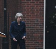 UK's May survives, weakened and with an exit date