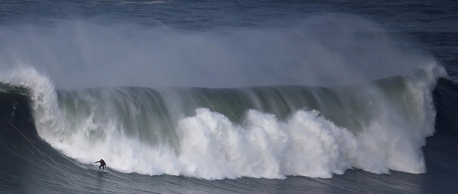 <p>A surfer drops in on a large wave at Praia do Norte in Nazare, Portugal, Nov. 19, 2016. (Photo: Rafael Marchante/Reuters) </p>