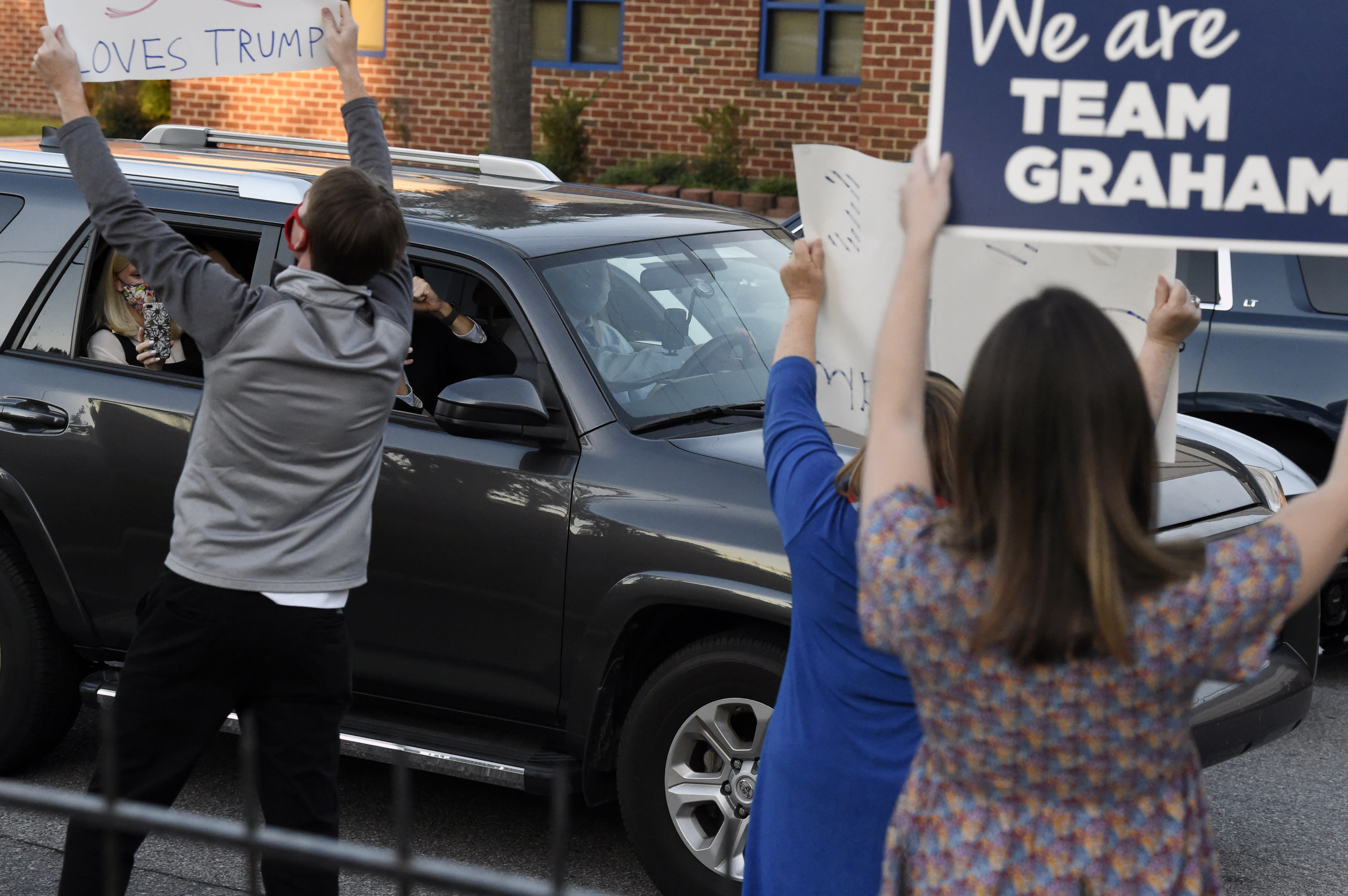 Supporters wave signs as U.S. Sen. Lindsey Graham arrives at the site of his first debate with Democratic challenger Jaime Harrison, Saturday, Oct. 3, 2020, at Allen University in Columbia, S.C. (AP Photo/Meg Kinnard)