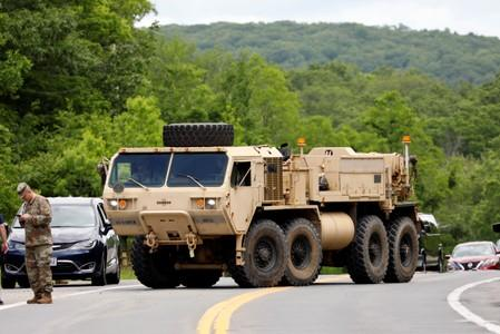 A heavy duty military vehicle enters the site of accident that killed at least one West Point cadet and injured nearly two dozen cadets in Highland Mills