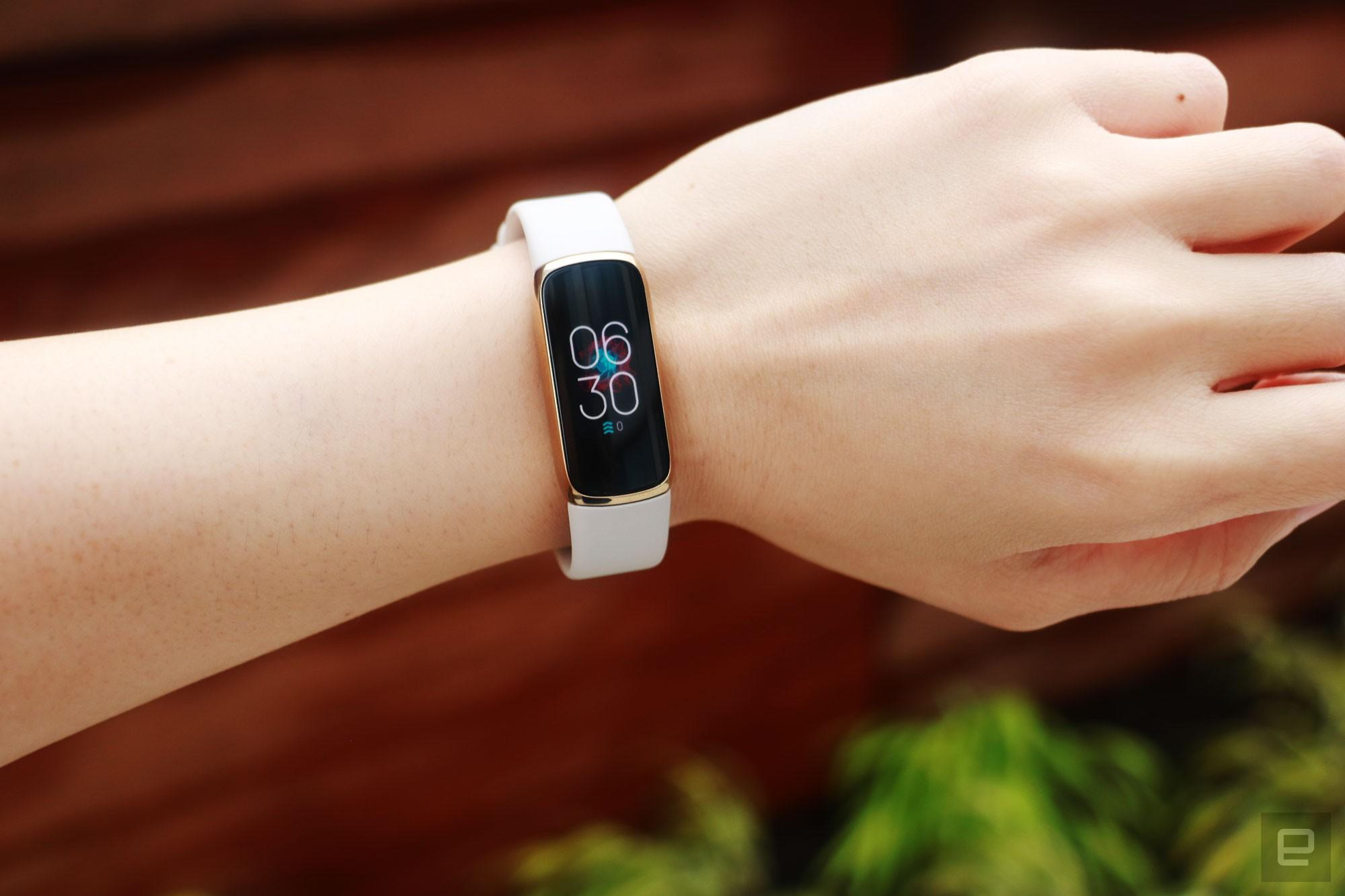 Front view of the Fitbit Luxe with a light pink silicone band on a wrist against a dark brown background with some greenery. The screen shows the time is 6:30pm.