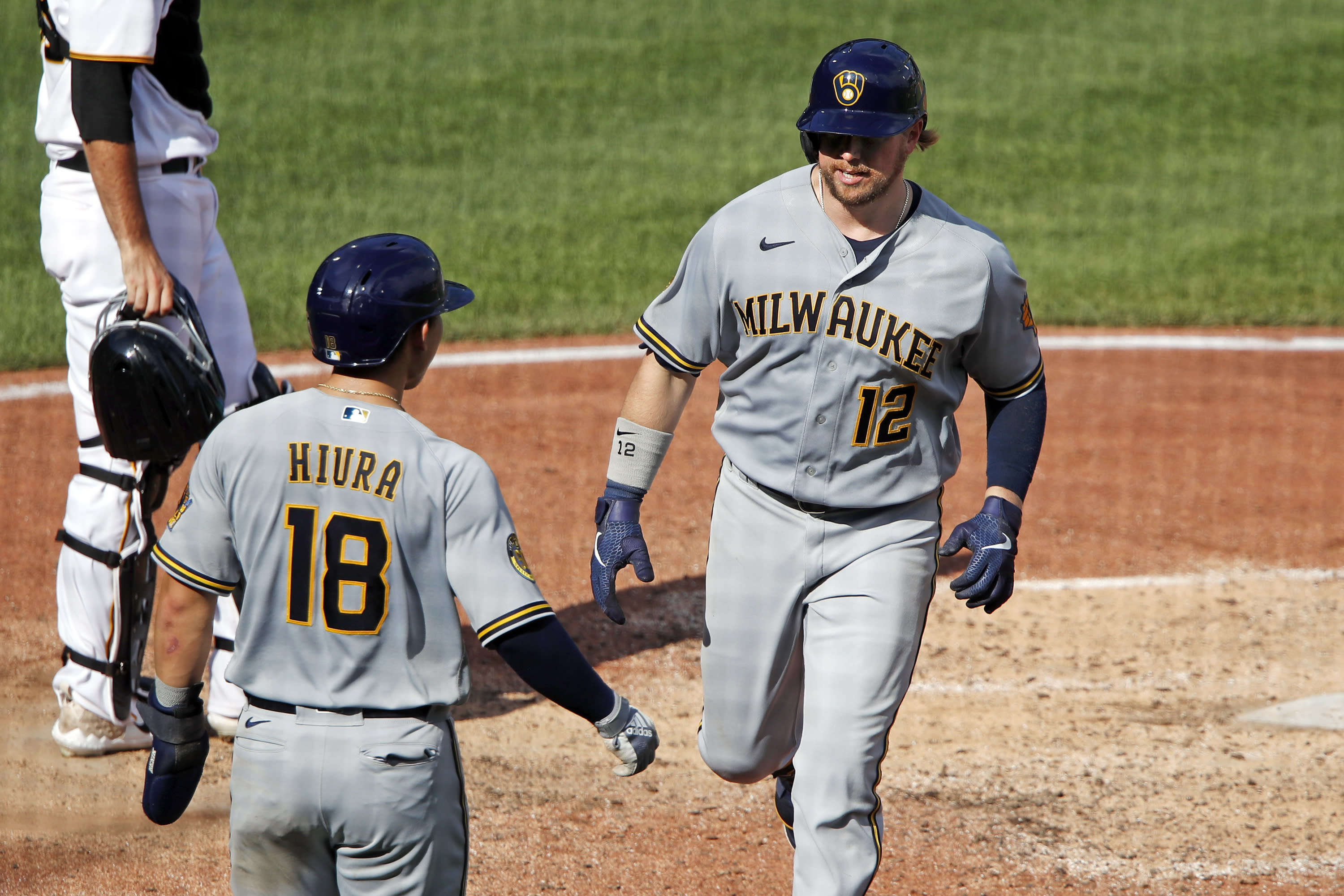 Milwaukee Brewers' Justin Smoak (12) celebrates with Keston Hiura as he heads for the dugout after hitting a two-run home run off during the sixth inning of a baseball game in Pittsburgh, Sunday, Aug. 23, 2020. (AP Photo/Gene J. Puskar)