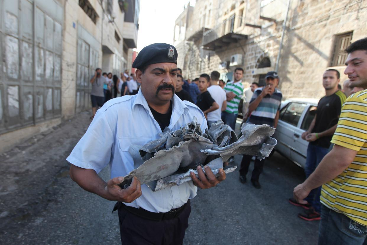 A Palestinian policeman carries the remains of a rocket fired by Palestinian militants from the Gaza Strip towards Israel after it hit by mistake a building in the West Bank town of Beit Sahur, near Bethlehem, on August 5, 2014 (AFP Photo/Musa Al-Shaer)