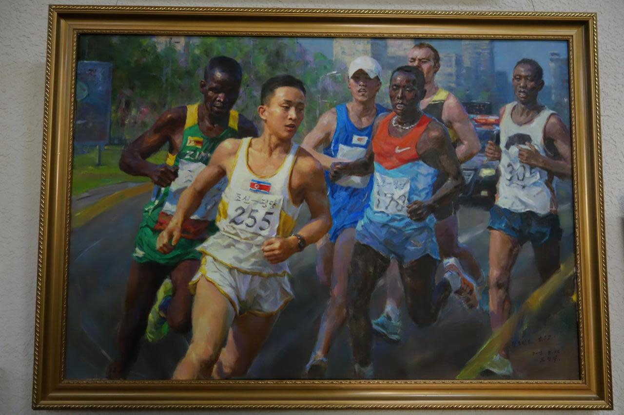 <p><i>A portrait of runners taking part in the Pyongyang annual marathon, hangs on the wall inside the capital's gallery.</i></p>