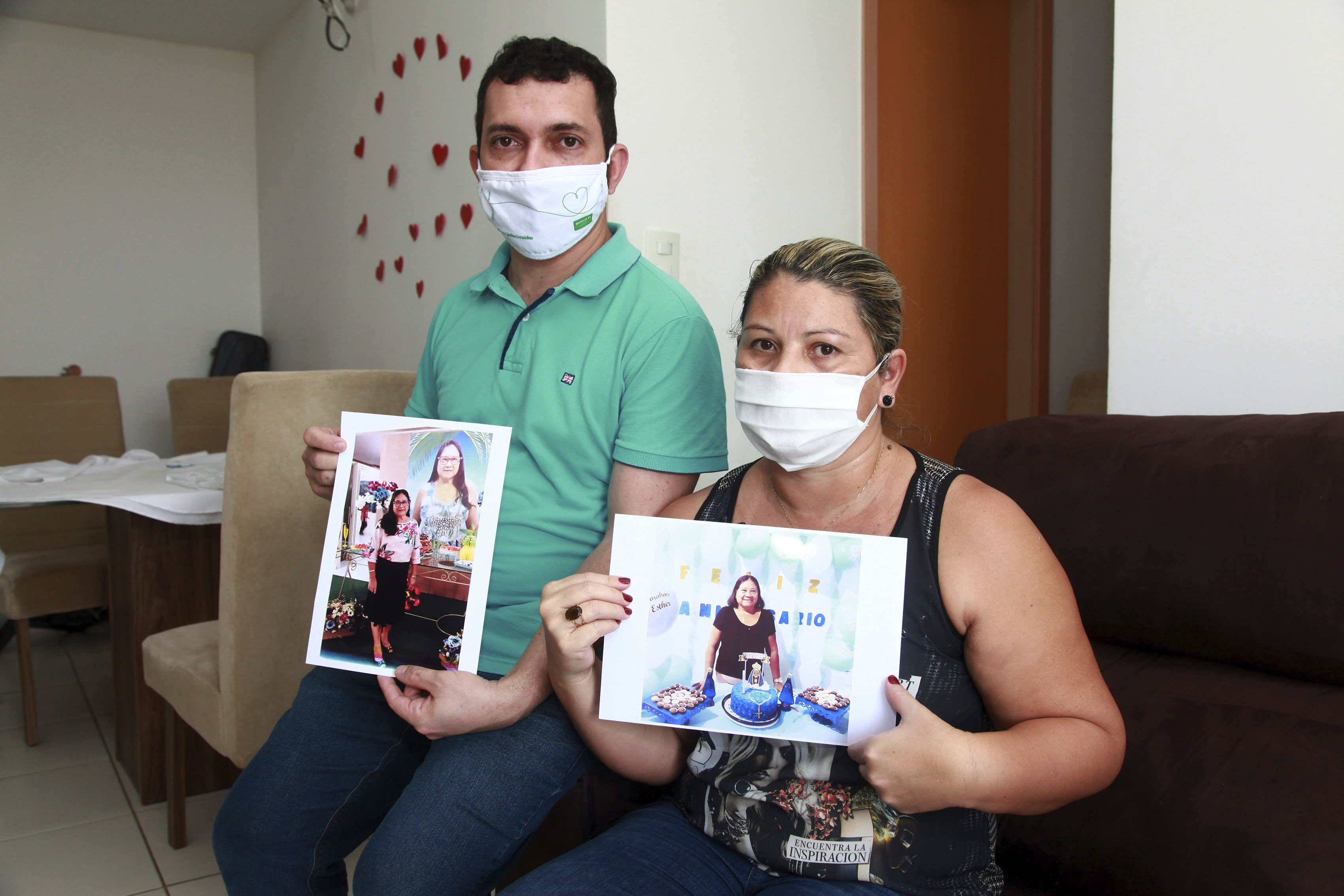 Luigi do Nascimento and his wife Viviane Melo da Silva, pose for a photo holding pictures of her mother Esther Melo da Silva, in their home in Manaus, Brazil, Tuesday, Aug. 4, 2020. Da Silva's 67-year-old mother was a healthy lady who loved to help others, go to the church and share her days with her kids and grandchildren. She died from COVID-19 on April 9, after five days in a public hospital. (AP Photo/Helton Belo)