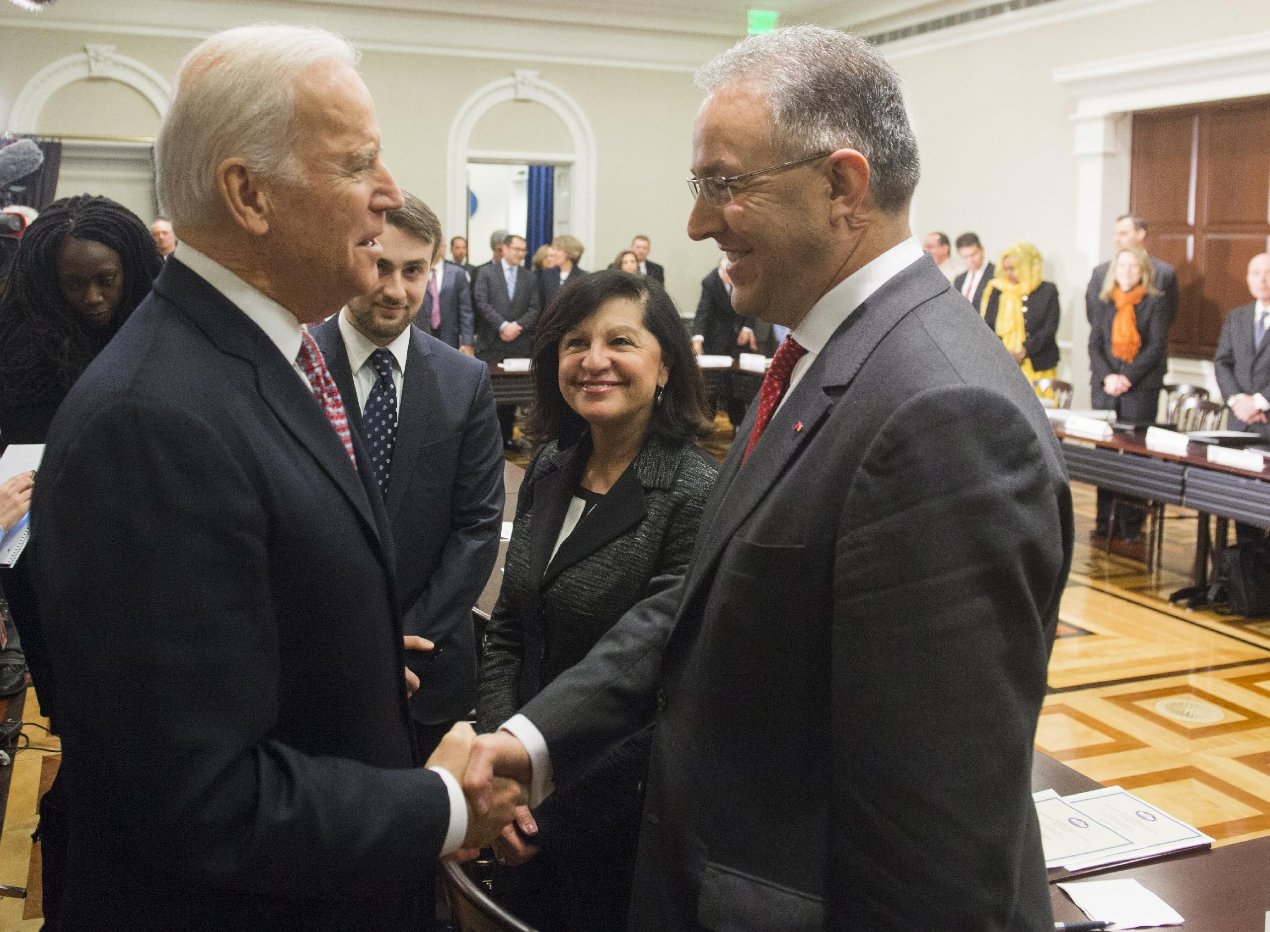 US Vice President Joe Biden shakes hands with Mayor Ahmed Aboutaleb of Rotterdam, Netherlands, during the opening session of the White House Summit in Washington, DC, February 17, 2015 (AFP Photo/Saul Loeb)