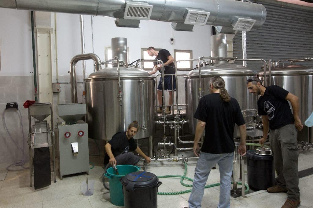 Israeli employees make gluten-free beer at the Meadan Brewing in the northern Israeli city of Karmiel (AFP Photo/Menahem Kahana)