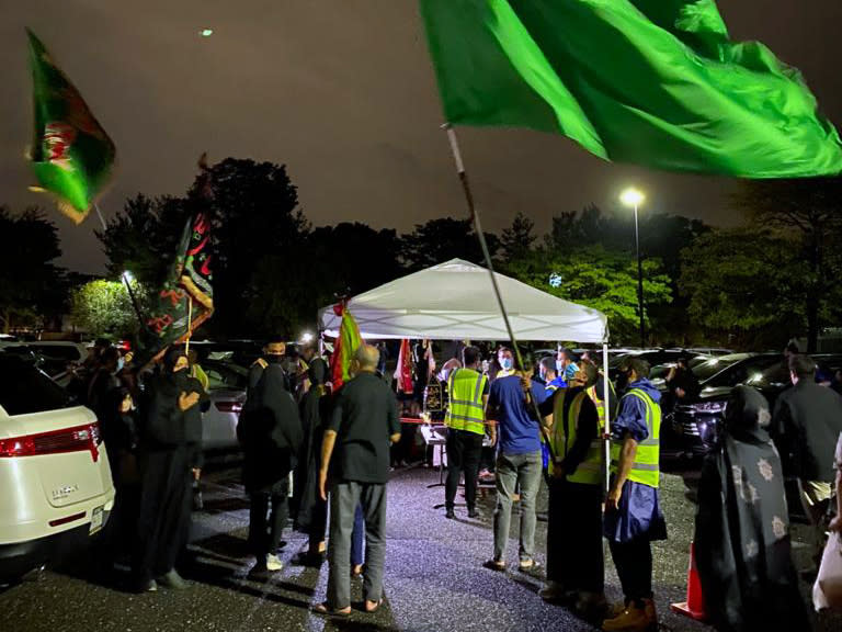 In a photo provided by Fatima Mukhi-Siwji, people gather with flags in a parking lot for a drive-in commemoration of the seventh-century death of Imam Hussein, Thursday, Aug. 27, 2020, in Hicksville, N.Y. Shiite Muslims are marking the mourning period in the shadow of the coronavirus. (Fatima Mukhi-Siwji via AP)(Fatima Mukhi-Siwji via AP)