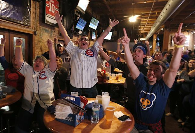 Fans celebrate while watching Game 7 at the Cubby Bear near Wrigley Field. (AP)