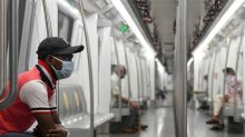 Commuters flash victory signs as India re-opens metro despite virus surge