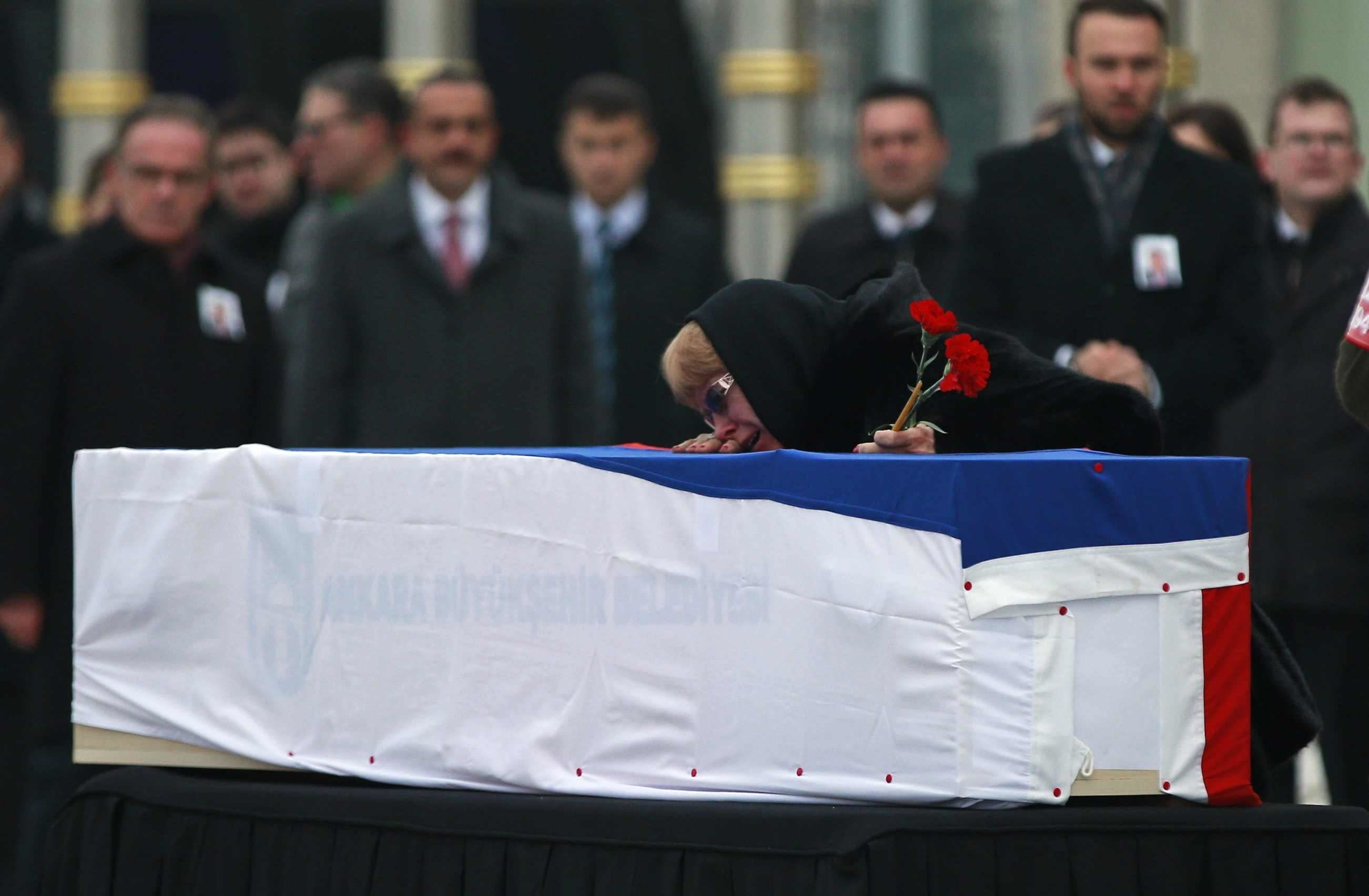 <p>The wife of Russian Ambassador to Turkey Andrey Karlov who was assassinated Monday, cries over her husband's coffin, draped in the Russian flag, during a ceremony at the airport in Ankara, Turkey, Tuesday, Dec, 20, 2016. (Photo: Emrah Gurel/AP) </p>