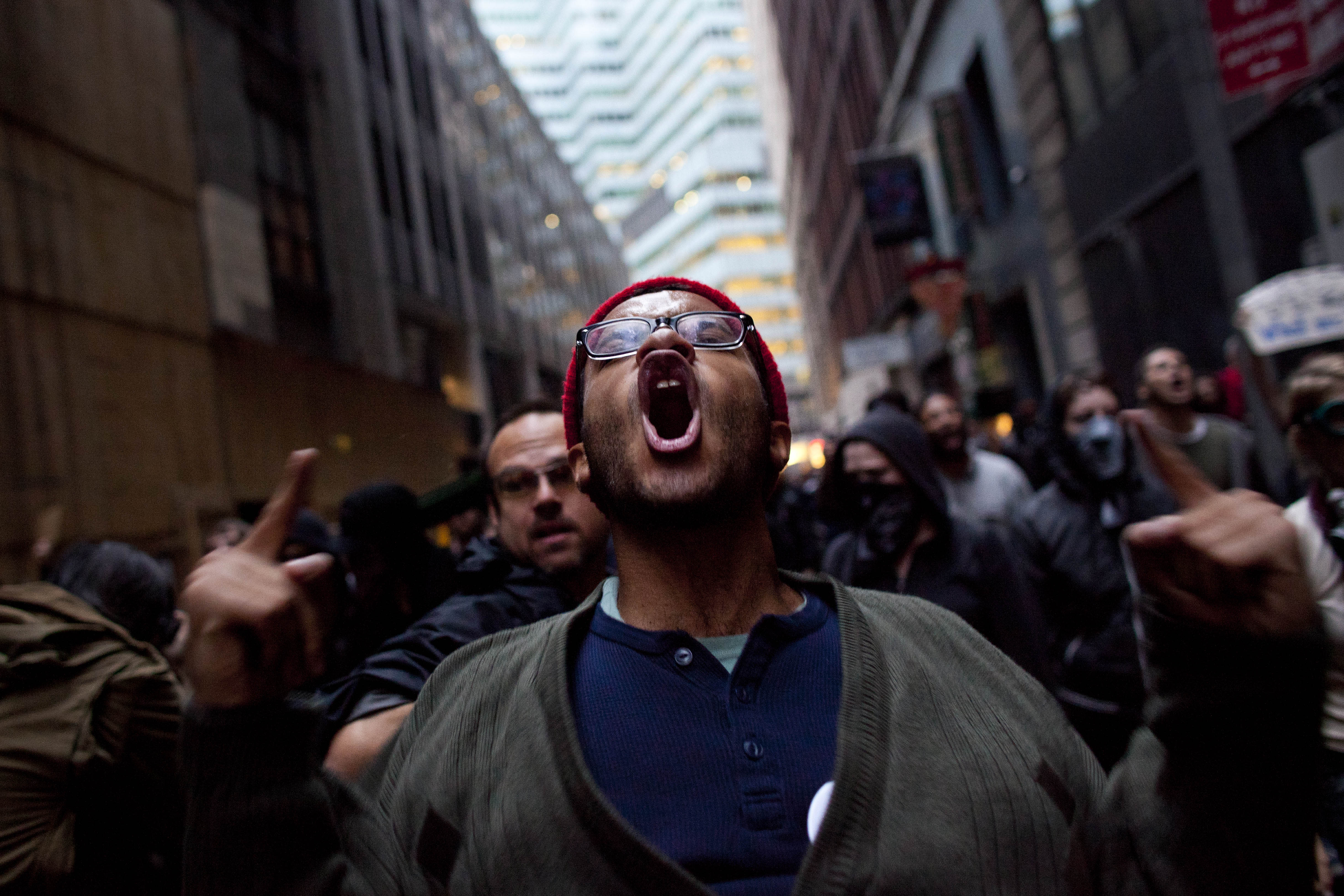 FILE - In this Friday, Oct. 14, 2011 file photo, a man participating in the Occupy Wall Street protests screams while marching towards Wall Street in New York. Americans, Republicans and Democrats alike, are asking some fundamental questions about the state of the union that go beyond how to grow the economy or curb foreclosures. Among the most profound: What is - and perhaps should be - the role of government in our lives? (AP Photo/Andrew Burton, File)