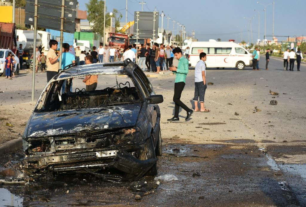 Iraqis walk past the site of a car bomb attack in Kirkuk city, a multiethnic flashpoint some 250 kilometres (155 miles) north of Baghdad, on April 15, 2018