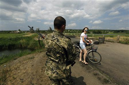 A woman smiles at a pro-Russian rebel guarding a rebel-held position on the outskirts of the eastern Ukrainian town of Slaviansk