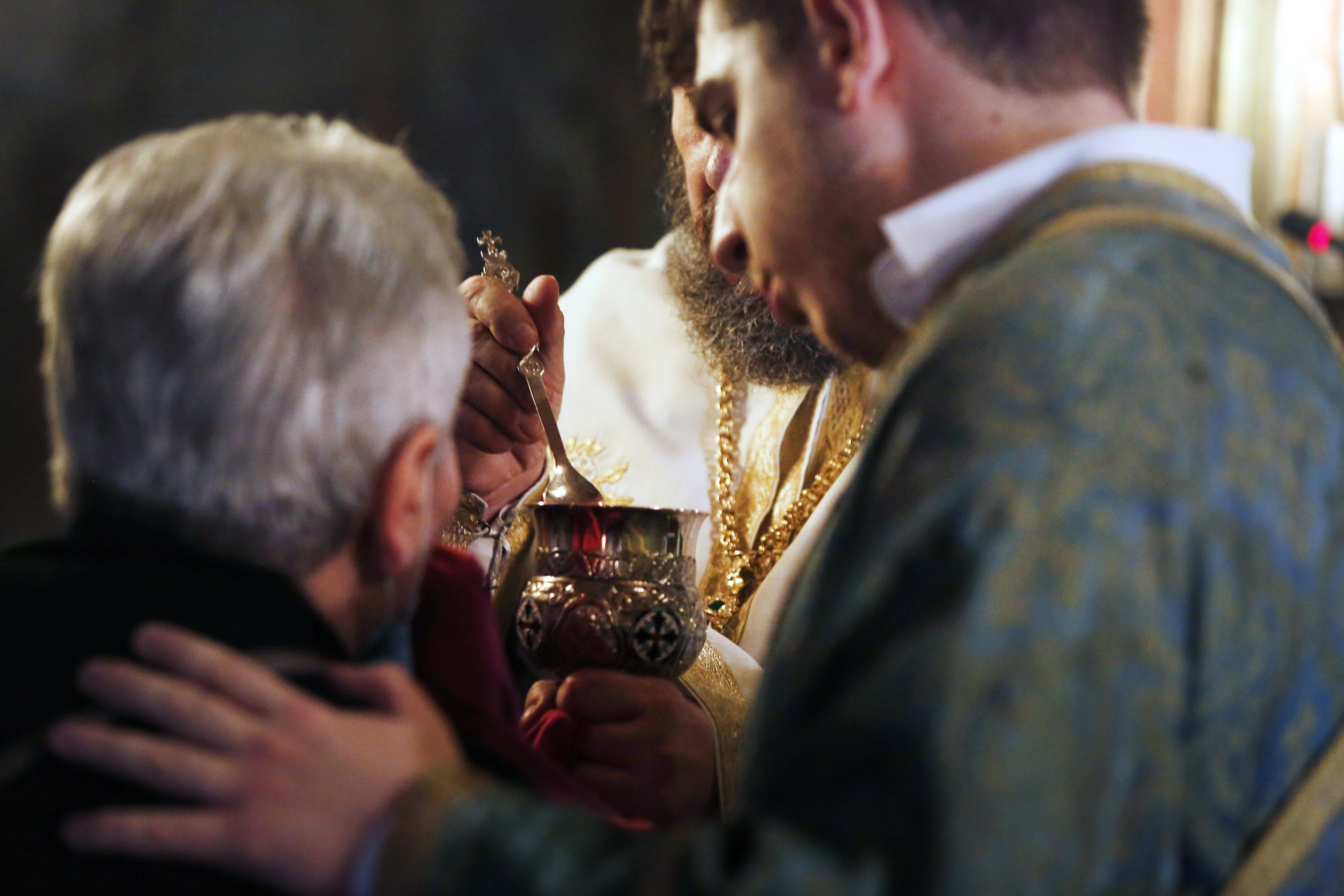 In this Sunday, May 24, 2020, photo, a Greek Orthodox priest uses a traditional shared spoon to distribute Holy Communion during Sunday Mass in the northern city of Thessaloniki, Greece. Contrary to science, the Greek Orthodox Church says it is impossible for any disease, including the coronavirus, to be transmitted through Holy Communion. (AP Photo/Giannis Papanikos)