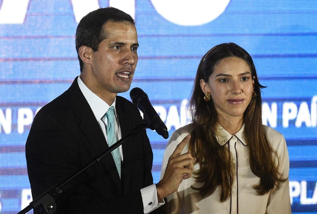 Venezuela's opposition leader Juan Guaido (L) accuses -- with his wife Fabiana Rosales by his side -- the country's security forces of trying to intimidate her