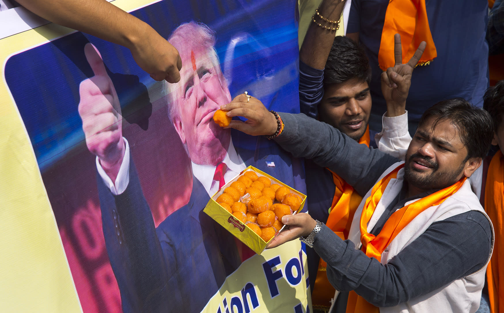 <p>Activists belonging to the Hindu Sena, or Hindu Army, a local organization, offer sweets symbolically to U.S. presidential candidate Donald Trump's poster in anticipation of his victory in New Delhi, India, Wednesday, Nov. 9, 2016. (AP Photo/Manish Swarup) </p>