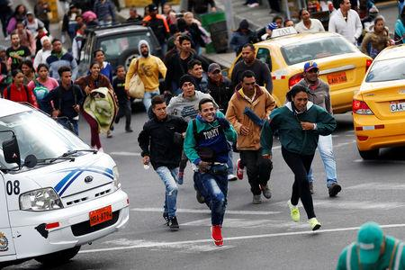Venezuelan migrants run to the line to register their exit from Colombia before entering Ecuador at the Rumichaca International Bridge, Colombia August 18, 2018. REUTERS/Luisa Gonzalez