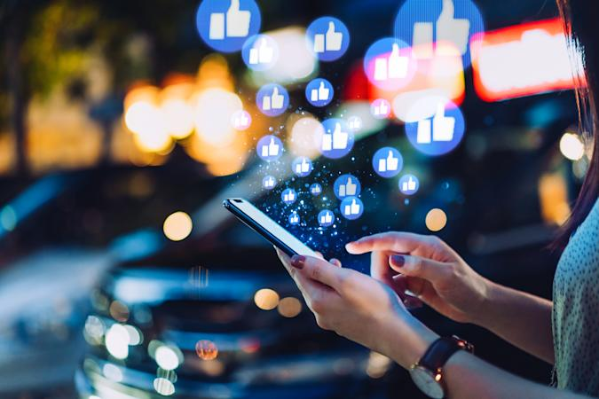 Cropped hand of young Asian woman using smartphone on social media network application on the go, viewing or giving likes in the city at night. Social media addiction concept