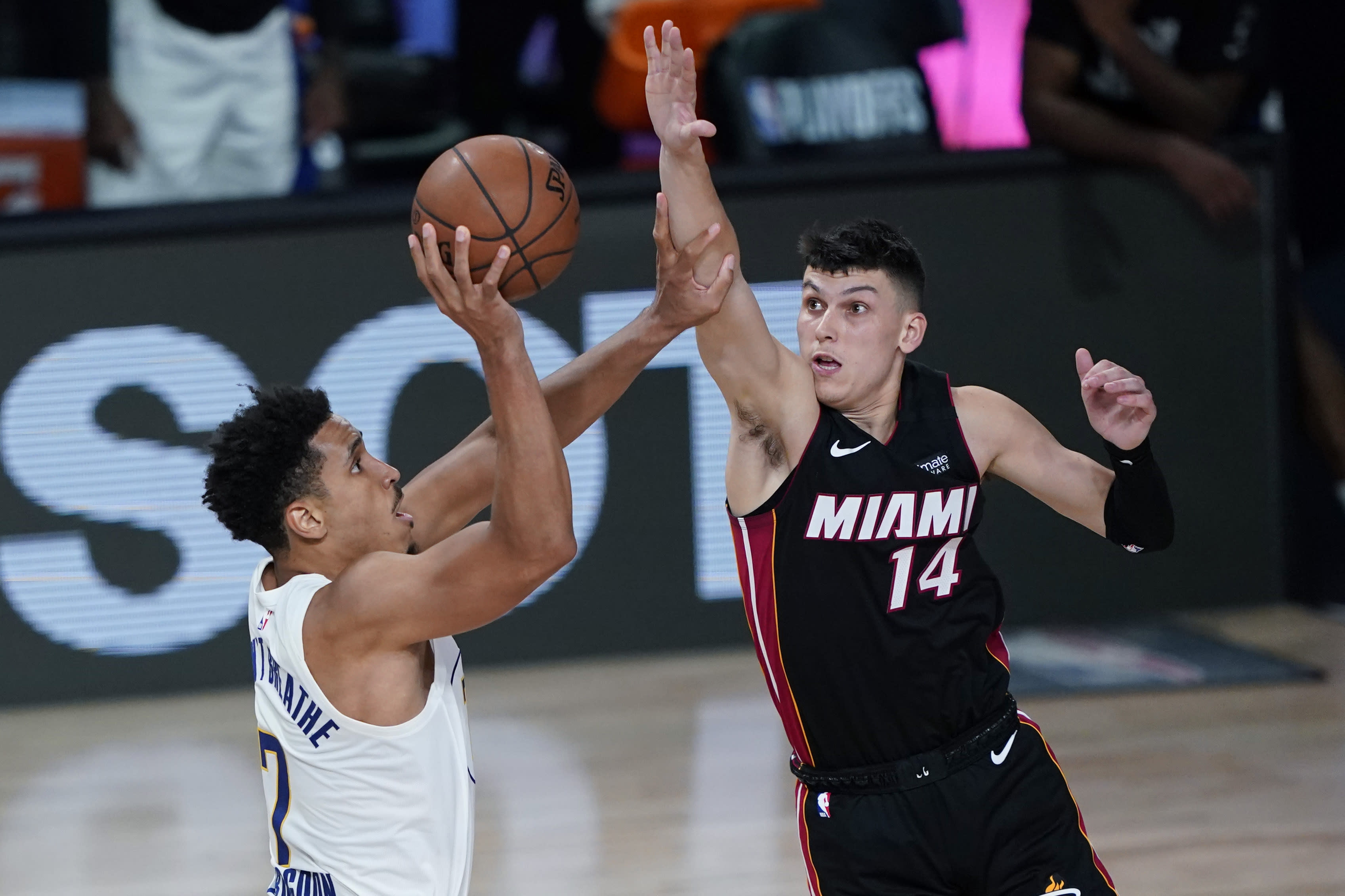 Indiana Pacers guard Malcolm Brogdon (7) shoots against Miami Heat guard Tyler Herro (14) during the second half of an NBA basketball first round playoff game, Saturday, Aug. 22, 2020, in Lake Buena Vista, Fla. (AP Photo/Ashley Landis, Pool)