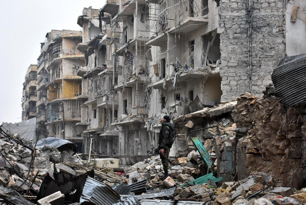 A member of the Syrian government forces stands in Aleppo's newly captured Al-Kalasseh district in the eastern part of the war torn city on December 13, 2016 (AFP Photo/George Ourfalian)