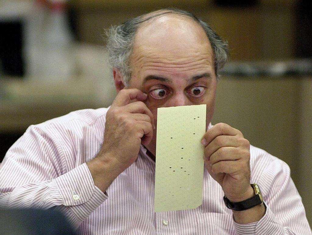 Broward County canvassing board member Judge Robert Rosenberg, pictured on November 24, 2000, looks over a questionable ballot at the Broward County Courthouse in Ft. Lauderdale, Florida (AFP Photo/RHONA WISE)