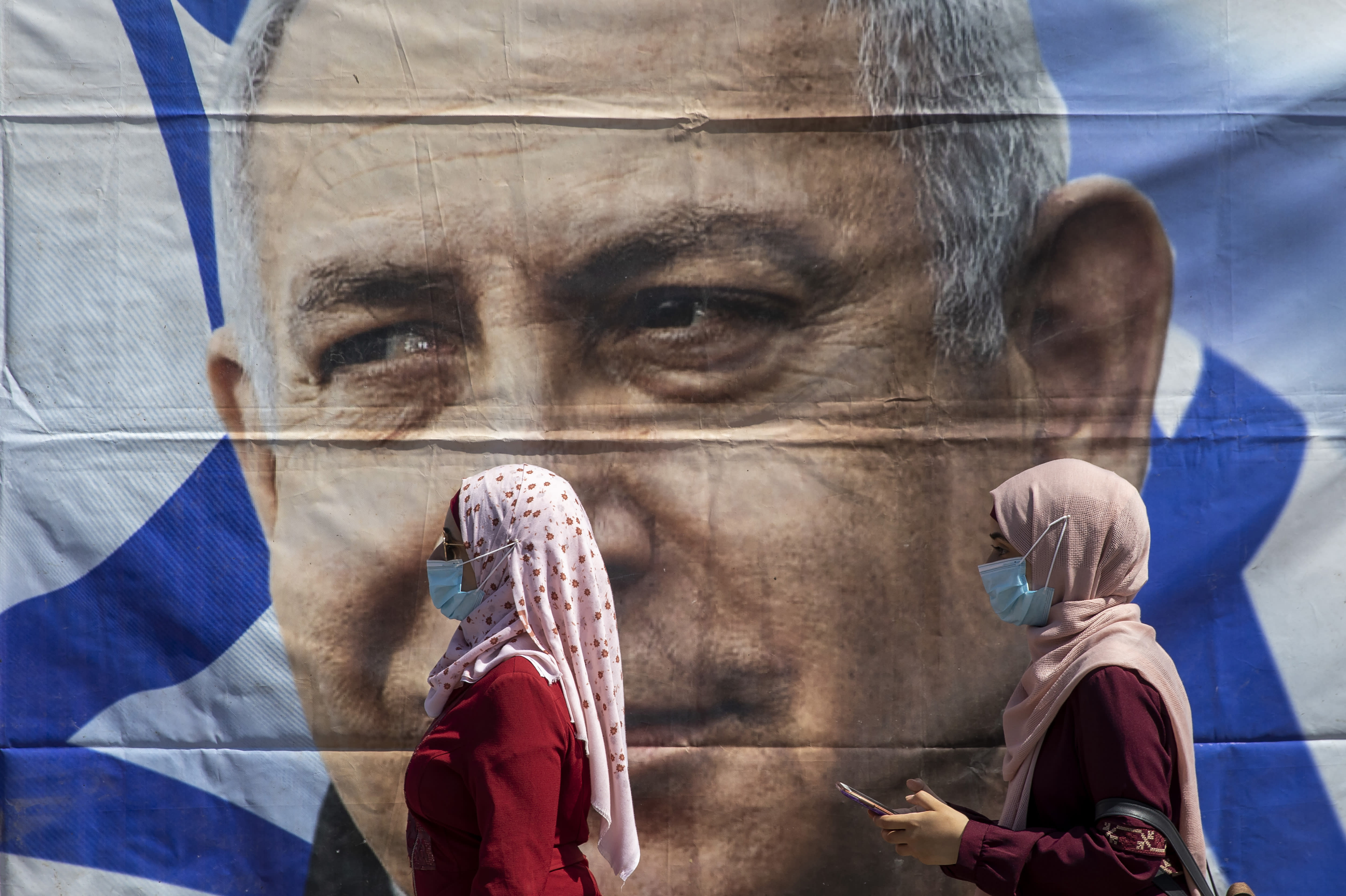 Muslim women wear face masks to help protect themselves from the coronavirus, walk past a poster hung by supporters of Prime Minister Benjamin Netanyahu outside the district court in Jerusalem, Sunday, July 19, 2020. The corruption trial of Netanyahu has resumed following a two-month hiatus. (AP Photo/Ariel Schalit)
