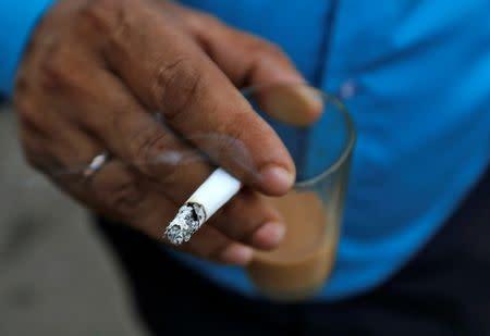 A man smokes a cigarette along a road in Mumbai