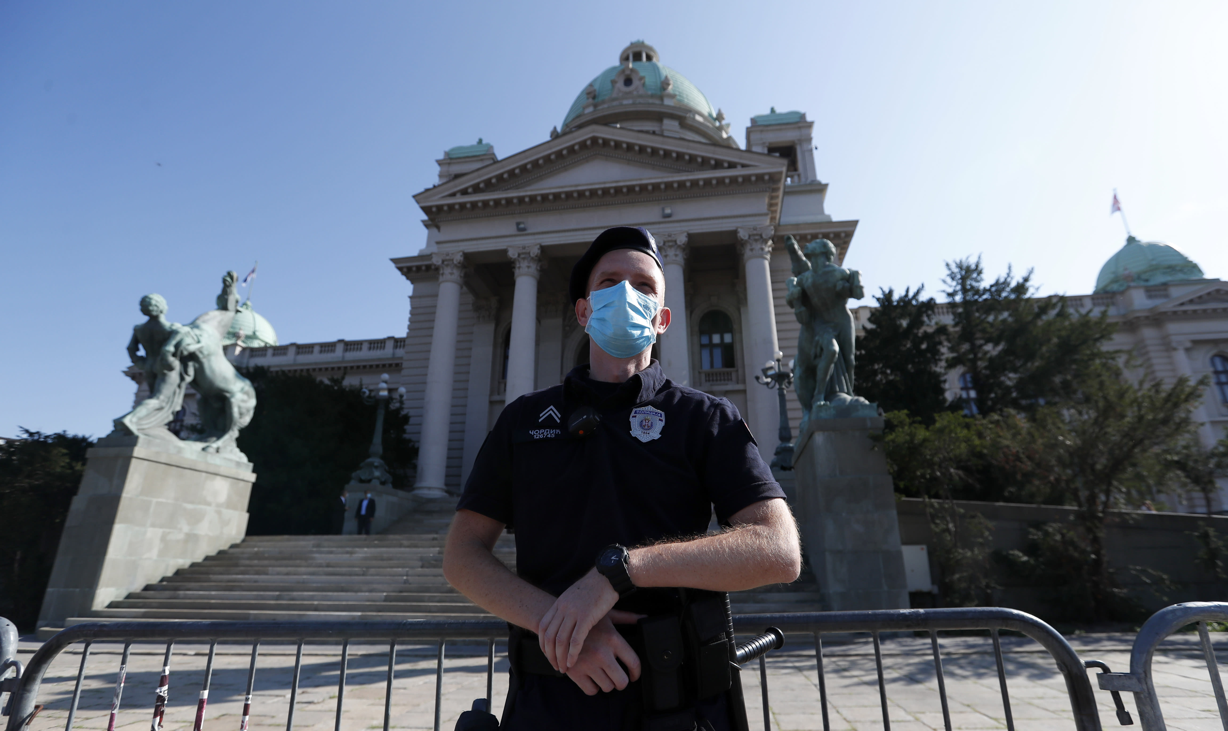 A Serbian police officer wearing a face mask to prevent the spread of coronavirus guards the parliament building before the inaugural parliament session in Belgrade, Serbia, Monday, Aug. 3, 2020. The Serbian parliament reconvened Monday amid protests by opposition and far-right supporters who claim the parliamentary election that was overwhelmingly won by the ruling populists was rigged. (AP Photo/Darko Vojinovic)