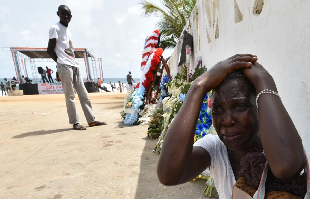 A woman cries next to wreaths of flowers in front of the Etoile du Sud hotel on March 20, 2016 during a tribute to the victims of an attack that killed 19 people on March 13 on Ivory Coast's Grand Bassam resort