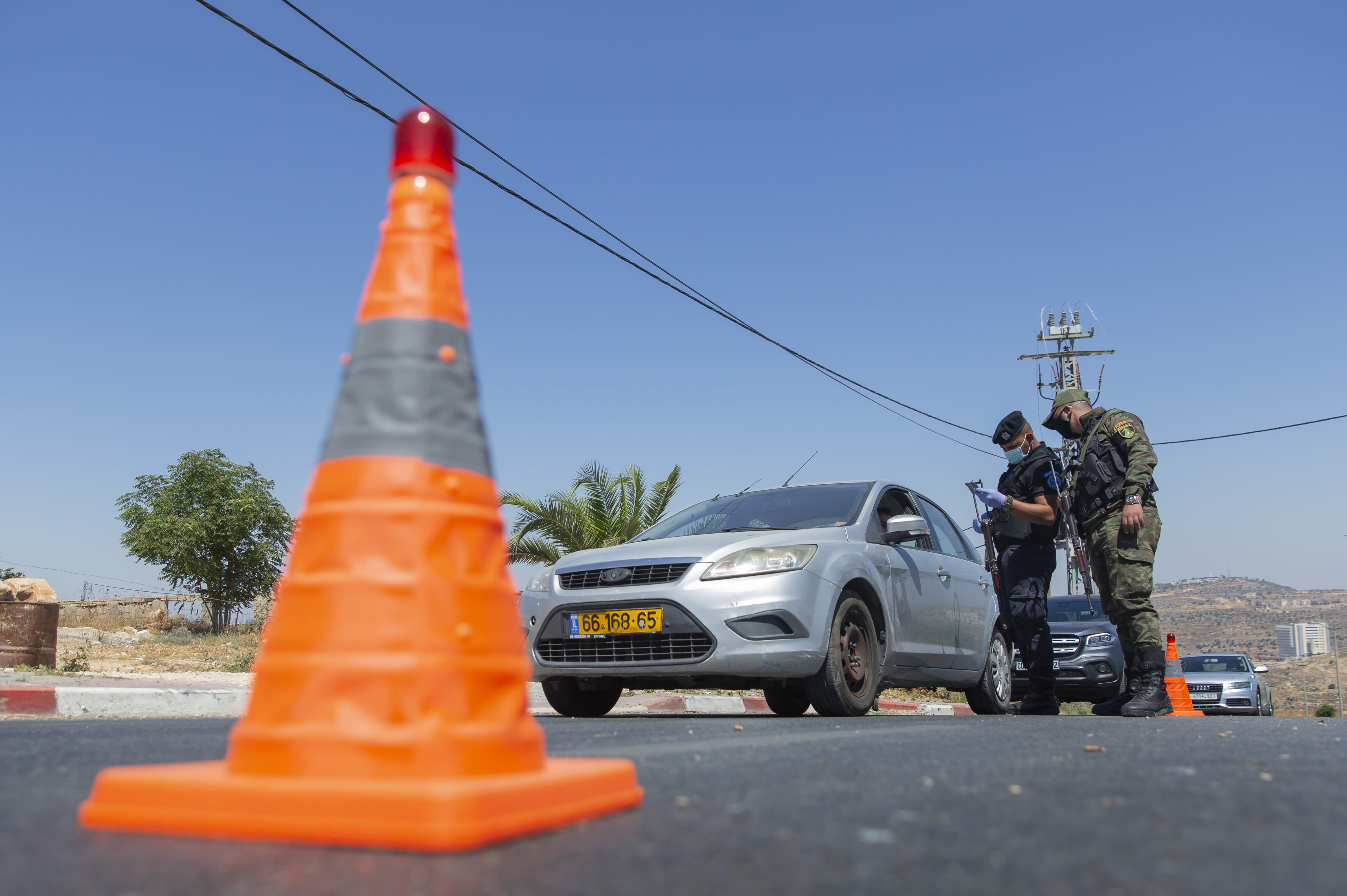 A Palestinian security unit mans a checkpoint at an entrance of in the West Bank city of Ramallah, Thursday, July 2, 2020. The Palestinian Authority has announced a five-day total lockdown in the West Bank starting Friday, in response to a major increase in coronavirus cases and deaths in recent days. (AP Photo/Nasser Nasser)