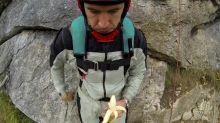 Base jumper casually eats banana while free-falling off mountainside