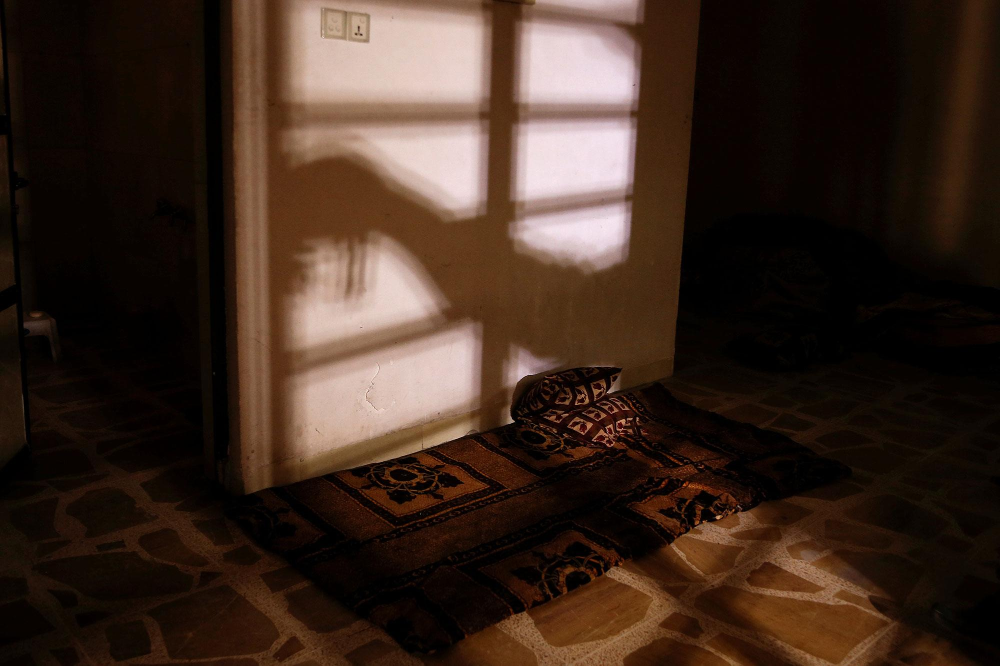 <p>The shadow of a member of the Iraqi Army's 9th Armoured Division is seen as he opens a steel gate to a room used as a cell for men, inside a compound used as a prison by Islamic State militants in the 17 Tamuz (July 17) district, in western Mosul, Iraq, June 6, 2017. (Alkis Konstantinidis/Reuters) </p>