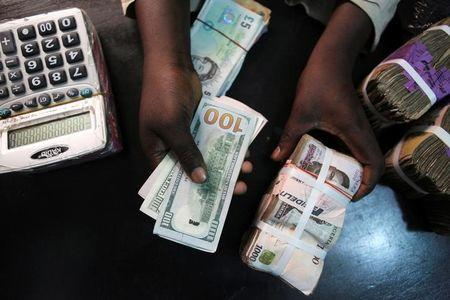A trader changes dollars with naira at a currency exchange store in Lagos